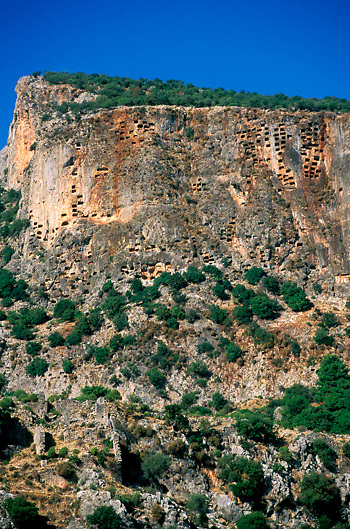 Rock cut tombs from the Lycian period dot the face of a giant cliff in Pinara near the Turquoise Coast of Southern Turkey