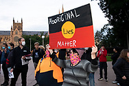 Protesters hold up signs in Hyde Park during a 'Black Lives Matter' rally on 02 June, 2020 in Sydney, Australia. This event was organised to rally against aboriginal deaths in custody in Australia as well as in unity with protests across the United States following the killing of an unarmed black man George Floyd at the hands of a police officer in Minneapolis, Minnesota. (Photo by Steven Markham/ Speed Media)