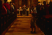 A child plays in the aisle as Mass is being held in a local rural Catholic church, on 15th October 1997, in Neubourg, Normandy, France.