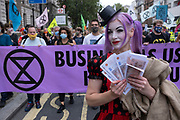 Protester with her 'dirty money' on Whitehall at Extinction Rebellion demonstration on 3rd September 2020 in London, United Kingdom. With government resitting after summer recess, the climate action group has organised two weeks of events, protest and disruption across the capital. Extinction Rebellion is a climate change group started in 2018 and has gained a huge following of people committed to peaceful protests. These protests are highlighting that the government is not doing enough to avoid catastrophic climate change and to demand the government take radical action to save the planet.