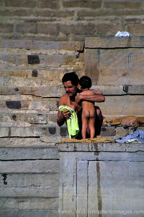 Asia, India, Uttar Pradesh, Varanasi. Father bathes his son in the Ganges River water in Varanasi.