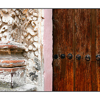Detail of stone sculptured pink orange wall next to old wooden paneled studded door;<br />