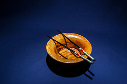 Hand turned wooden oak bowl on dark blue background with decorated black colored chopsticks