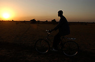 David Chulei, from the shiluk people, rides his bike back home to the Joseph Kore village in the shores of the Nile river, some 20 kilometers outside Malakal city, in Upper Nile state, where he works as a security guard. (PHOTO: MIGUEL JUAREZ LUGO).