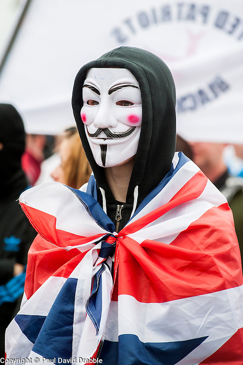 """Rotherham England<br /> 13 September 2014 <br /> Protestors wearing Anonymous mask and Union Flag outside Rotherham Town Hall before the start of the English Defence Leagues Justice for the Rotherham 1400 March on Saturday Afternoon described by an EDL Facebook Page as """"a protest against the Pakistani Muslim grooming gangs"""" on Saturday Afternoon <br /> <br /> <br /> Image © Paul David Drabble <br /> www.pauldaviddrabble.co.uk"""