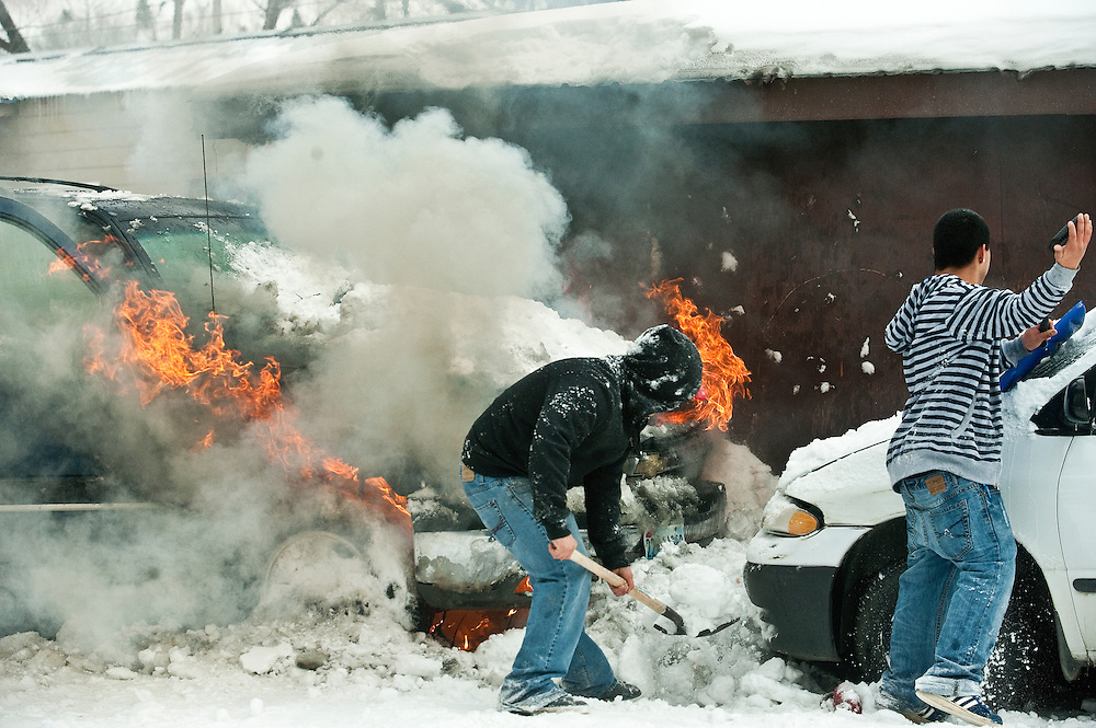 """PRICE CHAMBERS/JACKSON HOLE DAILY<br /> Armed with a shovel, Carlos Chavez, right, rushes to throw snow on his vehicle as it's engulfed in flame on Thursday at his home at 1175 Gregory Ln. """"All I saw was smoke coming out from under the hood,"""" Chavez said. """"I honestly couldn't tell you what happened."""" Chavez's neighbors helped by throwing more snow on the blaze until Jackson Hole Fire/EMS could respond."""