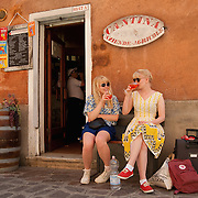 """VENICE, ITALY - JUNE 17:  Two tourists enjoy a Spritz (a powerful mixture of white wine, Campari and soda water) in front of a traditiona bacaro on June 17, 2011 in Venice, Italy. The bacari are the local down to earth version of wine bars, they serve  """"cicheti"""" a sort of Tapas, traditionally washed down with a glass of wine, and Venetians stop to snack and socialize before and after meals..."""