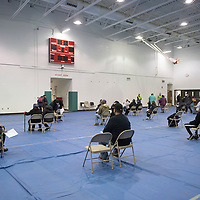 Patients sit and wait in the gymnasium on the University of New Mexico-Gallup campus following their vaccination for a 15 minute observation period during Gallup Indian Medical Center's COVID-19 vaccination event Saturday morning.