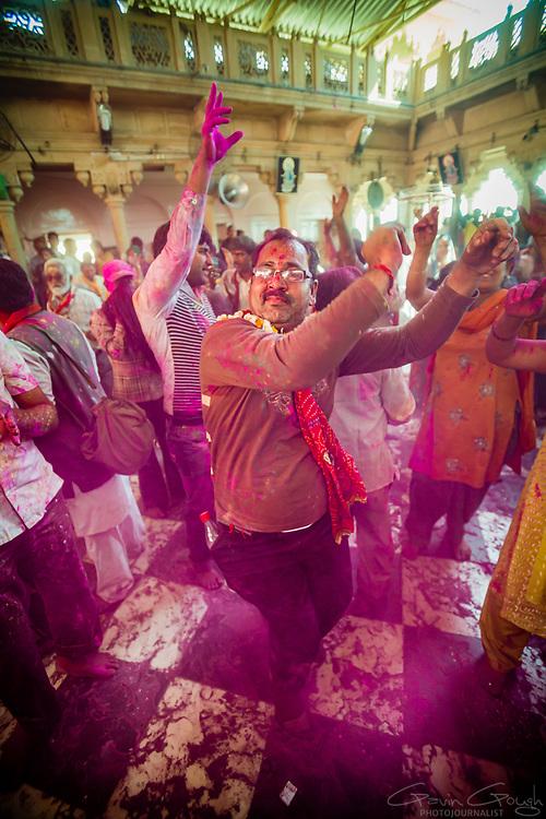 A man dancing during Hindu Holi celebrations inside the temple, Radha Rani Temple, Barsana, India