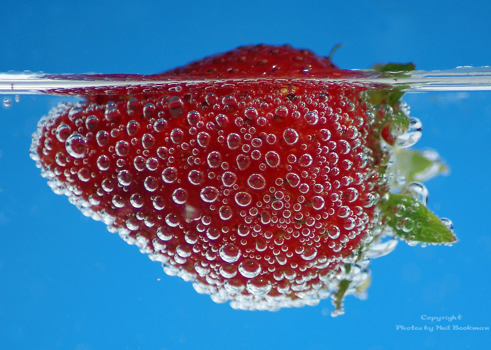 A strawberry floating in sparkling water.