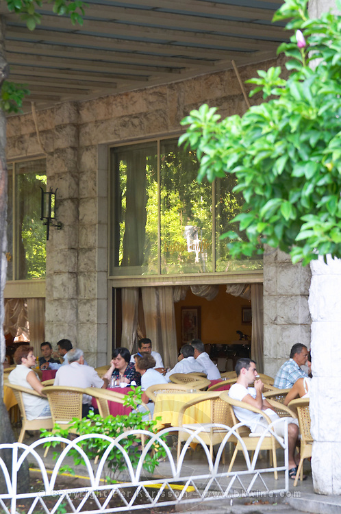 The cafe with outside seating terrace at the hotel Crna Gora. People sitting talking having coffee. Podgorica capital. Montenegro, Balkan, Europe.