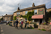 Hikers leave the village shop in Muker in Swaledale, which runs broadly from west to east. To the south and east of the ridge a number of smaller dales. Swaledale is a typical limestone Yorkshire dale, with its narrow valley-bottom road. Yorkshire, England, UK.
