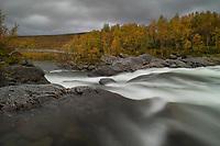 Bridge crossing flowing water of Vindelälven river along Kungsleden Trail, Lapland, Sweden
