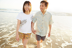 Lifestyle image of Japanese middle age couple having fun walking in ocean in Californian beach