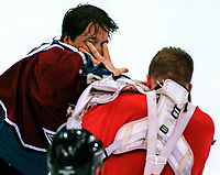 Colorado Avalanche goalie Patrick Roy, left, and Detroit Red Wings goalie Chris Osgood mid-ice fight in the third period at Joe Louis Arena in Detroit, Wednesday, April 1, 1998. -- Photo by Jack Gruber