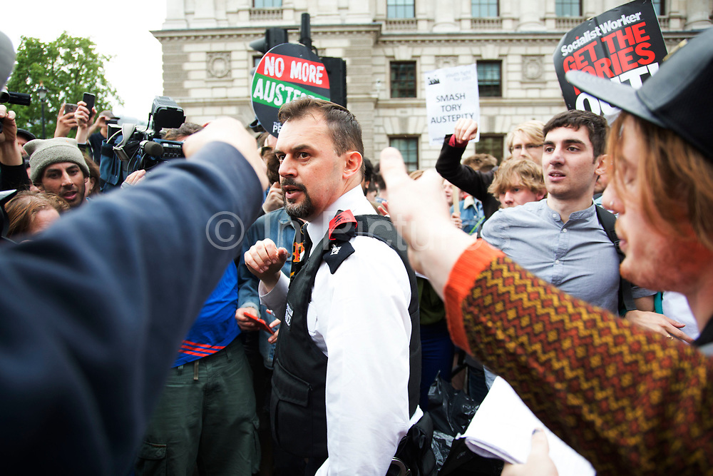London, UK. Wednesday 27th May 2015. Police scuffle with protesters as students demonstrate in Westminster against Tory Party cuts. The protest was focussed on a number of subjects including spending cuts but generally was a mark of displeasure and concern as to what the Conservatives will do while in power.