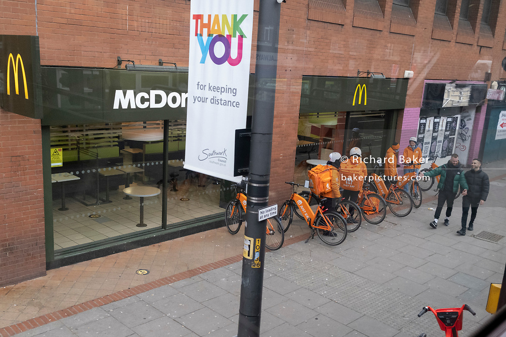 Gig economy 'Just Eat' delivery riders await their next takeaway orders outside the McDonalds on the Walworth Road in south London, during the third lockdown of the Coronavirus pandemic, on 22 February 2021, in London, England.