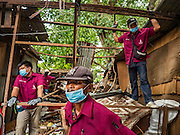 03 SEPTEMBER 2016 - BANGKOK, THAILAND: Bangkok city workers wait to tear down one of the 12 homes scheduled for demolition in the Pom Mahakan community. Hundreds of people from the Pom Mahakan community and other communities in Bangkok barricaded themselves in the Pom Mahakan Fort to prevent Bangkok officials from tearing down the homes in the community Saturday. The city had issued eviction notices and said they would reclaim the land in the historic fort from the community. People prevented the city workers from getting into the fort. After negotiations with community leaders, Bangkok officials were allowed to tear down 12 homes that had either been abandoned or whose owners had agreed to move. The remaining 44 families who live in the fort have vowed to stay.      PHOTO BY JACK KURTZ