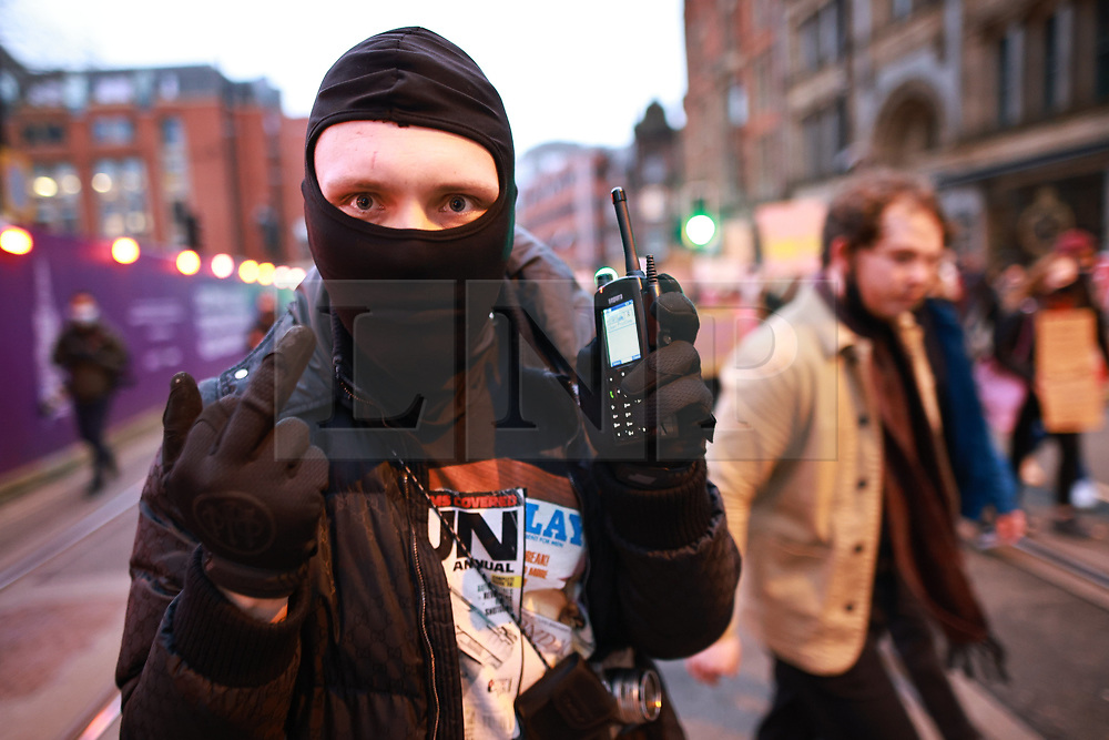 """© Licensed to London News Pictures. 20/03/2021. Manchester, UK. A man holding a radio, pulled from the uniform of a police officer, at the demo. """" Kill the Bill """" protest in St Peter's Square and across Manchester City Centre today, in opposition to the Police, Crime, Sentencing and Courts Bill 2021 that is currently before Parliament . Photo credit: Joel Goodman/LNP"""