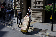 A middle-aged man carefully delivers boxes across a road junction in the City of London. Making his way down the street in the capital's financial hear, known as the Square Mile, the man balances the goods on a small trolley, trying not to tip the lot over, damaging the products. In the background are various businessmen either walking alomng London Wall (street) or talking on a phone in warm sunshine.