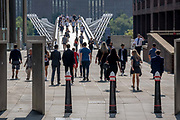 During the Coronavirus pandemic, Londoners and visitors to the capital walk through Peter's Hill, the end of which is the Millennium Bridge seen crossing the river Thames towards Tate Modern, on 16th September 2020, in London, England.