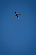 An Airbus 737-320 jet airliner G-EUYH with British Airways flies overhead in blue skies on its flight-path into London Heathrow airport, on 8th August 2018, in London, England.