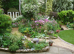 General view of garden at Ladywood with summer borders in full bloom, summerhouse and oval lawn.