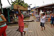 Fruit and vegetable vendors unload produce at the dock for a busy day at the market in Mancapuru, Brazil.