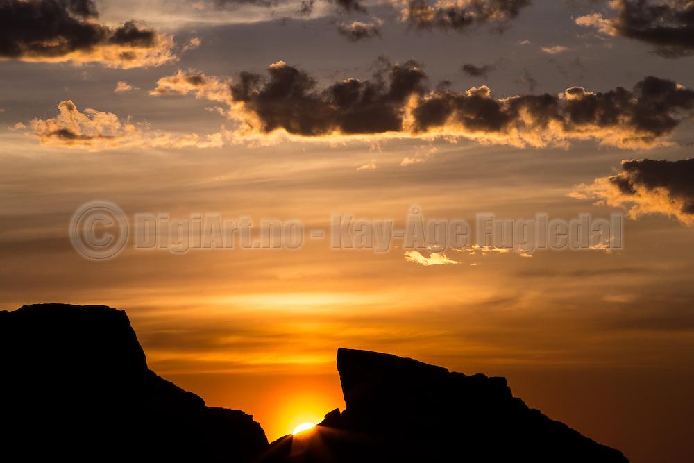 Sunset with the sun barely passes through a rock | Solnedgang der solen såvidt stikker opp bak et berg
