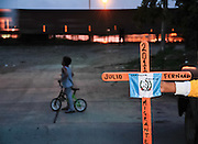 """A volunteer shows a cross with the flag of Guatemala near the train on August 9th,  2011, after guatemalan indigenous migrant Julio Fernando Cardona Agustín was murdered in Lechería, Estado de México. Cardona was arrested by police hours before his body was found dead and arrived with the caravan """"Paso a paso por la paz"""" (Step by step for peace). (Photo: Prometeo Lucero)"""