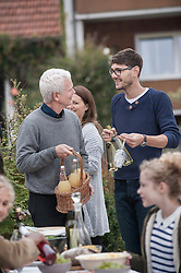 Father and son holding bottles of white wine and apple juice and talking at farmhouse, Bavaria, Germany