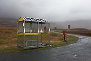 The remote bus stop at Kinloch crossroads, the junction of B8035 and A849 roads near Pennyghael, Isle of Mull, Scotland. As rain lashes this isolated location that looks towards the mountain pass of Glen More, we see the wet road surface that disappears into the distant moors in cloud and a lone postal box. Mull is served by two public bus companies, Bowmans and and R.N. Carmichael, the former's timetable shows an hourly or 2-hourly service. This shelter is on Bowmans 496 service from Craignure to Bunessan and Fionnphort on the Ross of Mull.
