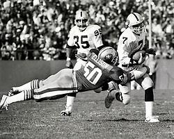 Los Angeles Raider quarterback Steve Beuerlein is .hit by San Francisco linebacker Riki Ellison. #35 is Raider Running back Steve Smith ( 1988 photo by Ron Riesterer)