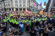 Police step up their efforts to disperse protestors at Oxford Circus junction during a two-week protest campaign in central London on Wednesday, Aug 25, 2021.  XR's protest campaign enters its 3rd day of activities putting at a halt the parts of important junctions in Britain's capital. XR launched a two-week protest campaign in London on Monday to demand that the government take greater action to address climate change. (VX Photo/ Vudi Xhymshiti)