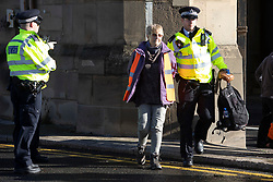 © Licensed to London News Pictures. 04/10/2021. London, UK. An arrested activist from Insulate Britain is walked away from the entrance to the Blackwall tunnel by a police officer after the group blocked the tunnel earlier this morning. Insulate Britain have successfully blocked various roads around the capital over a number of weeks, resulting in a court injunction banning them from going near the M25 motorway.  Photo credit: George Cracknell Wright/LNP