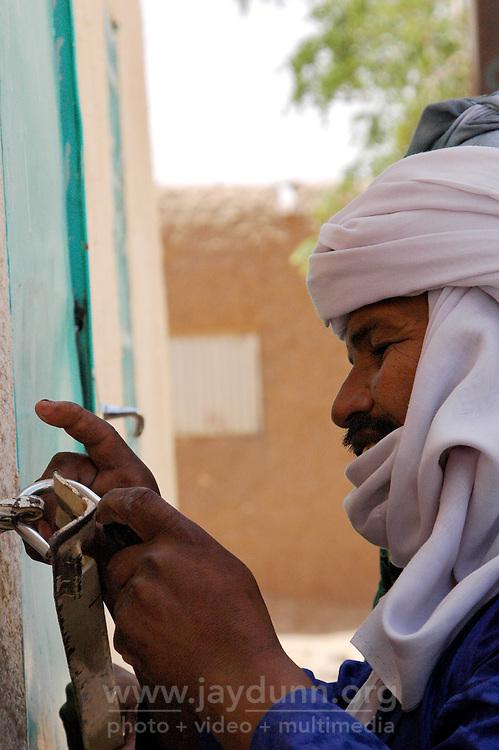 Niger,Agadez,2007. Rissa Ixa locks up Fatima Ixa's traditional handicrafts shop in the center of Agadez.