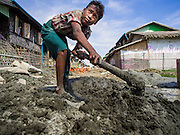 11 NOVEMBER 2014 - SITTWE, MYANMAR: A Buddhist boy patches the street in a Rakhine Buddhist IDP camp near Sittwe. About 700 Rakhine Buddhist families live in an Internal Displaced Persons (IDP) camp on the edge of Sittwe. The people in the camp lost their homes in Sittwe in 2012 when Buddhist mobs rioted and burnt down Rohingya Muslim homes and businesses. The Buddhists' homes were mistakenly destroyed by other Buddhists or intentionally destroyed by retaliating Muslims during the 2012 violence. Unlike the Muslims, who live in much larger camps further from Sittwe, the Buddhists are allowed to come and go into downtown Sittwe and their homes are built in the traditional style, on stilts with large windows, and so are much more comfortable.   PHOTO BY JACK KURTZ