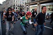 A large gathering of In Line skaters rollerblading up Regent Street en-masse. More than 200 skaters pass in this event promoting roller blading and free eco friendly travel in the city.