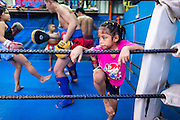 """18 DECEMBER 2104 - BANGKOK, THAILAND: A girl who wants to box works out after a sparring session at the Kanisorn gym. The Kanisorn boxing gym is a small gym along the Wong Wian Yai - Samut Sakhon train tracks. Young people from the nearby communities come to the gym to learn Thai boxing. Muay Thai (Muai Thai) is a Thai fighting sport that uses stand-up striking along with various clinching techniques. It is sometimes known as """"the art of eight limbs"""" because it is characterized by the combined use of fists, elbows, knees, shins, being associated with a good physical preparation that makes a full-contact fighter very efficient. Muay Thai became widespread internationally in the twentieth century, when practitioners defeated notable practitioners of other martial arts. A professional league is governed by the World Muay Thai Council. Muay Thai is frequently seen as a way out of poverty for young Thais and Muay Thai camps and schools are frequently crowded. Muay Thai professionals and champions are often celebrities in Thailand.     PHOTO BY JACK KURTZ"""