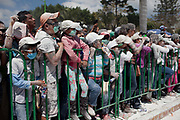 A line of people covered in talcum powder, behind a barrier. The annual Carnival in Zoque Coiteco, a district of Chiapas in Southern Mexico happens in the five days preceeding Ash Wednesday along with Carnival throughout the Americas. Participants dress in colourful costumes with masks depicting famous political and entertainment figures, and throw talcum powder at each other.