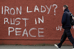 A pedestrian walks past graffiti that reads 'Iron Lady? Rust in Peace' referring to former British prime minister Margaret Thatcher in west Belfast, Northern Ireland, on 9th April, 2013 a day following Thatcher's death. Britain stood deeply divided over the legacy of former prime minister Margaret Thatcher as it made preparations for the grand funeral next week of the woman known around the globe as the 'Iron Lady', Belfast, Great Britain, 9th April, 2013.  Photo by Paul McErlane / i-Images. ..<br /> <br /> File photo - One year ago: Baroness Thatcher died.<br /> On Tue, Apr 8 2014 it will be one year since the Longest-serving UK Prime Minister of the 20th century, the first and only woman to serve in the role to date, died on April 8, 2013  after suffering a stroke.