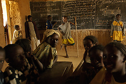 Mahmoud stands in front of the chalk board as they wait for their teacher to arrive in a classroom in the  village of Intedeyne March 15, 2007.    the challenge to educate children in Mali still exists and particularly for girls. Female literacy rates never reach even 50 percent of male literacy rates. Mali has the highest percentage of people living below the poverty line in any country in the world. Ninety percent of Malians survive on less than two dollars a day.