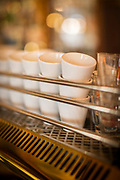 Close-up of espresso cups on top of traditional coffee machine, Trieste, Italy