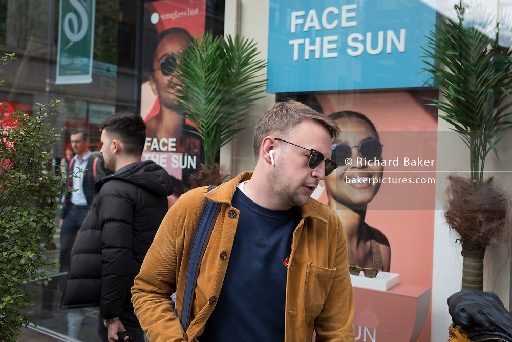A passerby-by wearing shades walks past the window of the Sunglass Hut retailer in Covent Garden whose current slogan is 'Face the Sun', on 15th June 2019, in London, England.