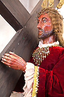 Scultpure of Jesus with a Giant Wooden Cross with a decidedly brown complexion