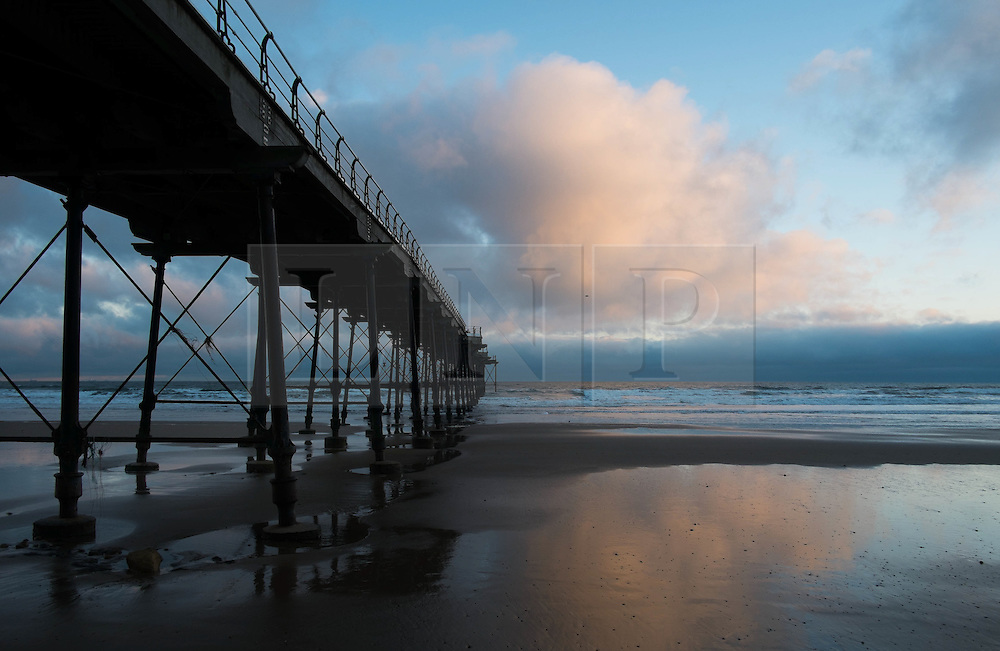 © Licensed to London News Pictures. 10/03/2014<br /> <br /> Saltburn, Cleveland, United Kingdom<br /> <br /> Out to sea beyond the pier a cloud catches the first rays of the sun at first light in Saltburn by the Sea in Cleveland.<br /> <br /> Photo credit : Ian Forsyth/LNP