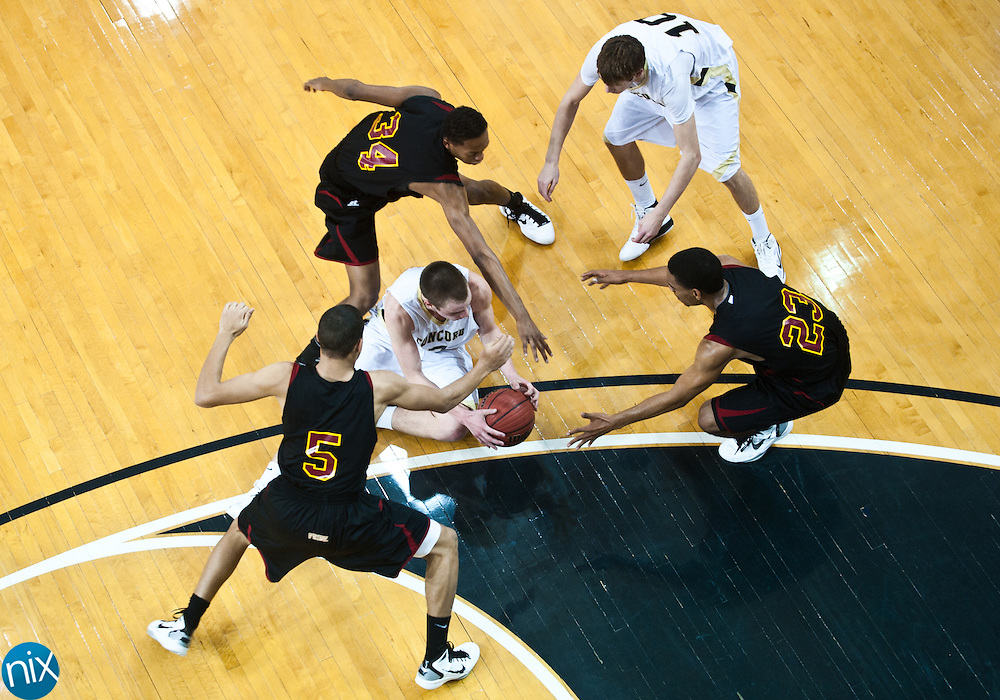 Concord's Kendall Knorr goes after a loose ball surrounded by Hickory's C.J. Wardrick (5) Denxel Dillingham (23) and Darius Malbon (34) during the regional round of the NCHSAA 3A playoffs Thursday night at the University of North Carolina at Greensboro. Hickory won the game 95-82 to end the Spiders season. (Photo by James Nix)