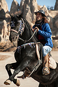Ekram with his pride and joy, a coal black stallion he has owned since a foal and keeps stabled in a cave cut into the volcanic rock formations that define the Cappadocia landscape.