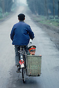A man and his young son in a basket with a Mao hat travel down a road near the town of Zigong in the Sichuan Province of China.