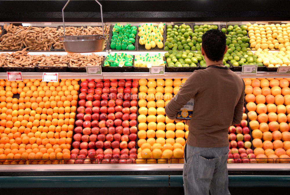 A young man examines the fruit section of a supermarket..